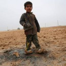 A child stands at a new refugee camp set up for Iraqis, mostly fleeing the northern city of Mosul on the outskirts of the Syrian town of Ras Al Ain, near the border with Turkey, on February 2, 2016.